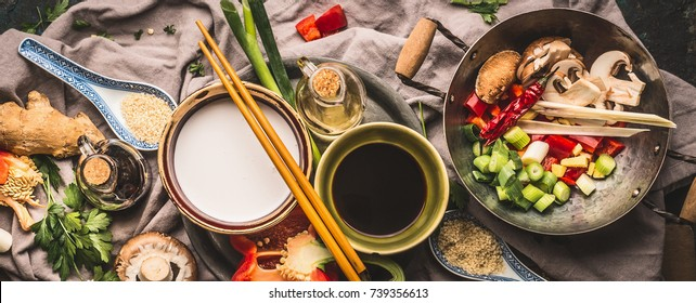 Vegetarian stir fry ingredients: chopped vegetables, spices,coconut milk, soy sauce,,wok and chopsticks, top view, banner. Asian food , Chinese or Thai cuisine concept
