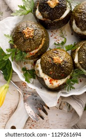 Vegetarian stuffed zucchini. Baked round courgettes, stuffed with rice, mushrooms and cheese with the addition of aromatic herbs in a baking dish on a wooden white table, top view