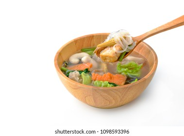Vegetarian Sukiyaki in broth mixed sea food (virtual) its make from tofu with vermicelli, vegetables in wood bowl, on spoon ready to eat, white background, diet food.