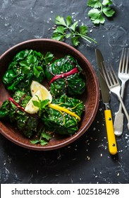 Vegetarian swiss chard packets. Chard leaves stuffed with  lentils and garden vegetables on a dark background, top view. Vegetarian healthy food concept