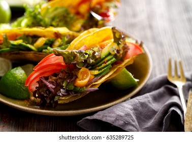 Vegetarian  tacos with avocado, tomatoes, onion and lettuce