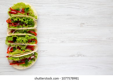 Vegetarian tacos made with lettuce, pepper, onion and tomato on white wooden background. From above. Top view