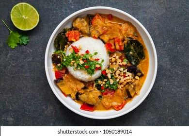Vegetarian Thai curry with aubergine and red pepper, rice, coriander and roasted peanuts