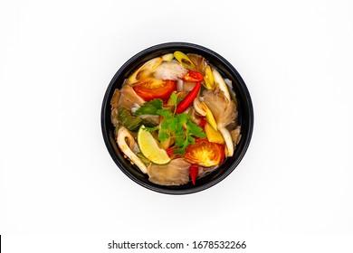Vegetarian Thai sour clear soup called Mushroom Tom Yum in black bowl on white background, Ingredients mushroom chilli lemon lemon grass Kaffir lime leaves Galangal and Coriander.