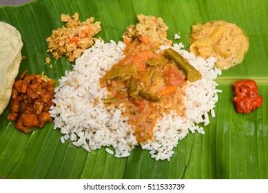 Vegetarian thali meals served on banana leaf, traditional south indian cuisine. Onam/vishu sadhya, boiled rice, served with curries Sambar, Rasam, Papadum, Payasam, Banana, Yogurt or Buttermilk, chips