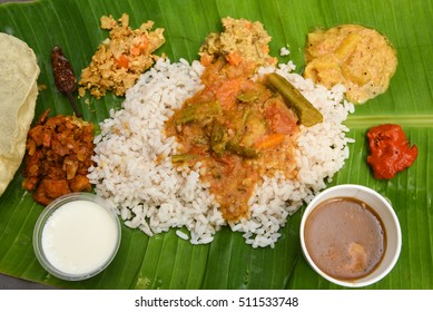 Vegetarian thali meals served on banana leaf, traditional south indian cuisine. Onam/vishu sadhya, boiled rice, served with curries Sambar, Rasam, Papadum, Payasam, Banana, Yogurt Kerala, chips