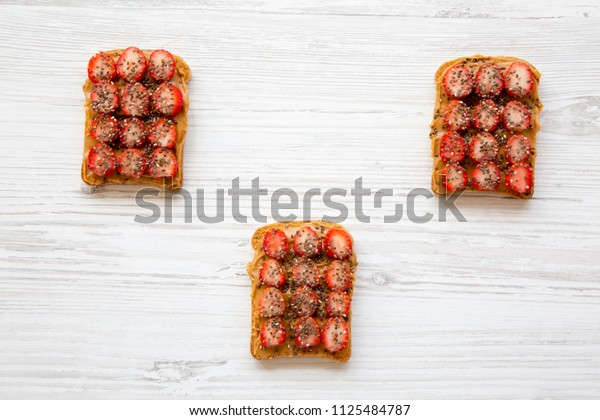 Vegetarian toasts with peanut butter, strawberries and chia seeds on a white wooden background, top view. Healthy breakfast.