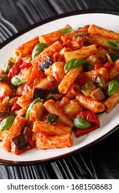 Vegetarian Tortiglioni pasta with vegetables and basil in tomato sauce close-up in a plate on the table. vertical