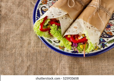 Vegetarian tortilla home with tomatoes, cabbage, lettuce and cheese on a blue plate. Mexican food.