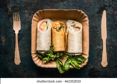 Vegetarian tortilla wraps in paper plate and wooden cutlery on dark background, top view, close up. Healthy lunch snack or street food concept