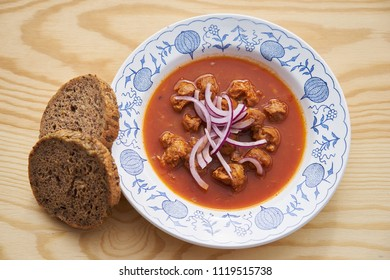 Vegetarian or vegan food or meal made from soya chunks in traditional goulash style with choped red onion served on rustic plate with wholecorn bread as a side dish.