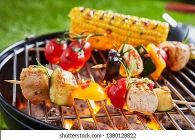 Vegetarian or vegan kebabs with tofu on the barbecue grilling over a hot fire outdoors with tomatoes and corn on the cob