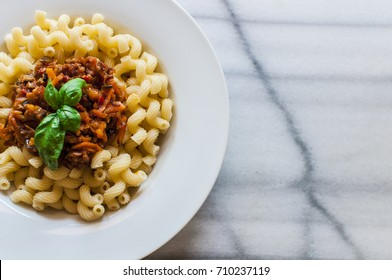 Vegetarian Vegetable pasta Spirali with zucchini, carrots, tomatos and basil in white bowl on marble table