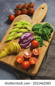 Vegetarian vegetables are sliced on a cutting board, cherry tomatoes, spinach, cabbage, pear, and cilantro.