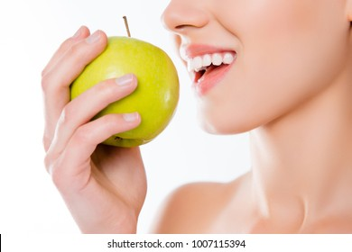 Vegetarian vitality wellbeing wellness concept. Cropped close up photo of white clean clear healthy woman's teeth trying to bite hard juicy green tasty apple in hand isolated on white background