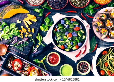 Vegetarian winter food on dark wood background top view - Variety of broccoli in a pan surrounded by  seasonal vegetables - Autumn vegan recipes and colorful sauces on rustic table - Vintage filter