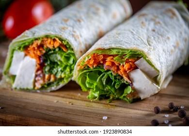 Vegetarian wrap sandwich on wooden background