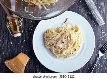 Vegeterian italian pasta: spaghetti with garlic oil, red chili and parmesan in white plate on wood table background. Bottle of olive oil and big bowl with pasta near it