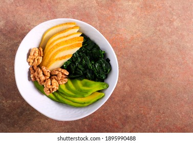 Veggie bowl with avocado, spinach, pear and walnuts