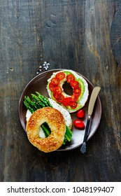Veggie breakfast sandwiches flat lay. Avocado, soft cheese, tomatoes and aspargus on bagels over wooden copy space background. Top view. Weight loss, clean eating, detox food concept