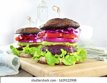 Veggie burger with guacamole, topped  with Portobello Mushroom.