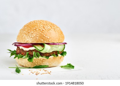 Veggie burger on a white paper and deck with leaves and seeds. Horizontal photo with copy space. Vegetarian diet concept.