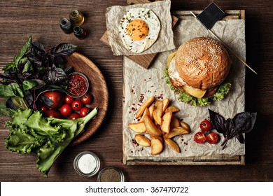 Veggie burger with salad, tomato and fries. Wooden background