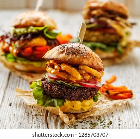Veggie burgers, homemade vegan burger with fresh and grilled vegetables and aromatic curry sauce on a white rustic table. Conception of a healthy diet, healthy alternative