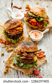 Veggie burgers, homemade vegan burgers with fresh and grilled vegetables and aromatic  sauces on a white rustic table. Conception of a healthy diet, healthy alternative