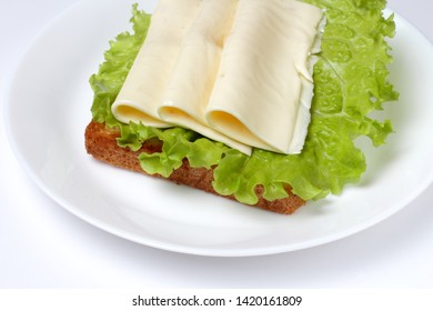 Veggie sandwich with lettuce and pieces of cheese on a large plate on a white background, bright natural colors.