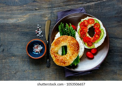 Veggie sandwiches plate flat lay. Avocado, soft cheese, tomatoes and aspargus on bagels over wooden copy space background. Top view. Weight loss, clean eating, detox food concept
