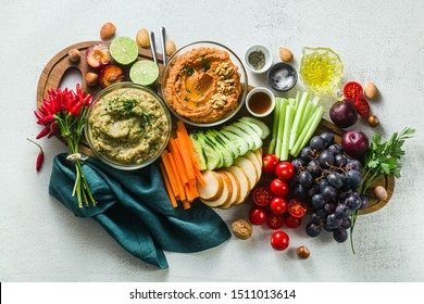 veggie serving table with snacks with vegetables, fruits, baba ganoush and dip or spread of roasted red pepper and nuts. healthy vegan food for celebration or friends. shot from above. copy space