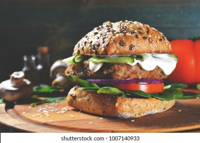 veggie, vegan burger with buckwheat, tomato, onion, vegan mayonnaise and spinach on a fresh bun with flax seeds and sesame, surrounded by spinach leaves, mushrooms, tomato, black pepper and spices.