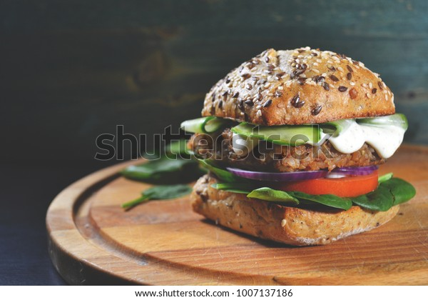 veggie, vegan burger with buckwheat, tomato, onion, vegan mayonnaise and spinach on a fresh bun with flax seeds and sesame, surrounded by spinach leaves