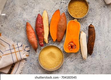 Veggies roots overhead sweet potato orange and cream color with yucca cassava pumpkin butternut squash over marble table cooking ingredients