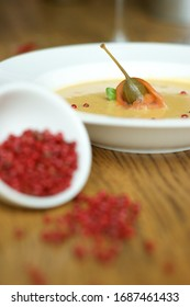 Vegitable, yellow soup with seeds of red pepper and green caper involute with salmon in the white plate on the bright wooden table