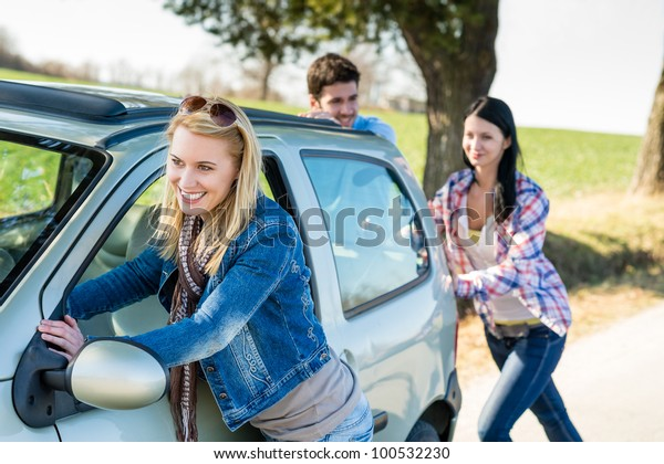 Vehicle breakdown young people pushing car down the road