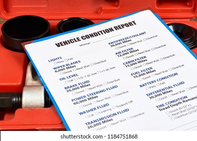 Vehicle condition report form against the background of automotive tools. Close up.