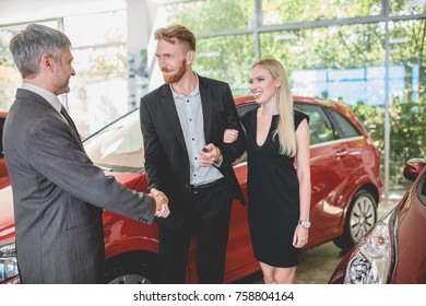 Vehicle dealer passing keys from new car to happy young couple. Male bying new car to wife.