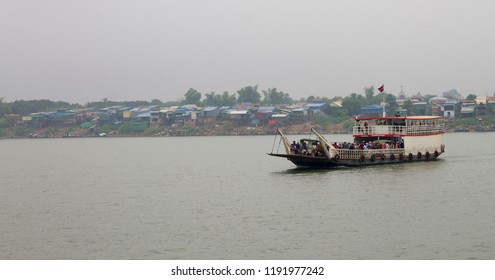 A vehicle ferry filled with cars, motorbikes and people crosses the Mekong River near a shanty town in Phnom Penh, Cambodia.