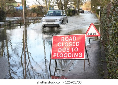 Vehicle ignoring road closed because of flooding sign.