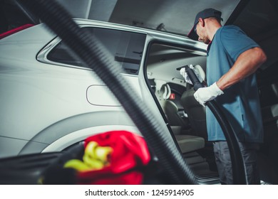 Vehicle Interior Vacuuming by Caucasian Cleaning Station Worker.
