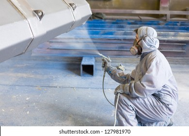 vehicle painter spraying white color on construction bucket
