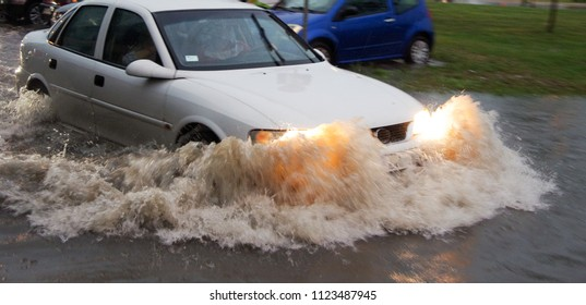 The vehicle passes through a flooded area, a flooded street.