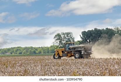 Vehicle spreading lime fertilizer onto a farm field