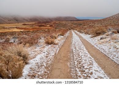 vehicle tracks in snow on brown dirt road in desert landscape misty morning Sierra Nevadas, California