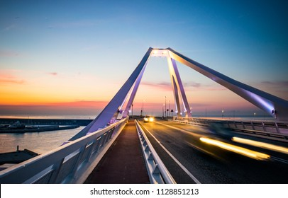 Vehicle Traffic and Pedestrian Pathway on Modern Bridge above Barcelona's Harbour at Dawn - Barcelona, Spain
