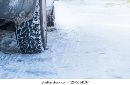 Vehicle wheels on a snowy road. Winter car tires on the icy road with snow.