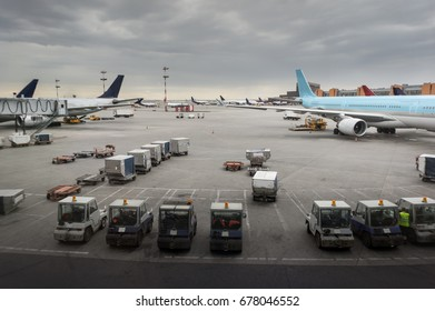 vehicles and ariplane parking in airport ramp in cloudy sky.