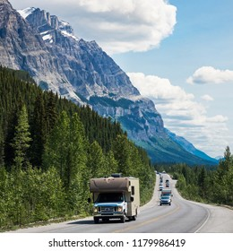 Vehicles driving down the iconic Icefields Parkway route between Banff and Jasper National Parks in Alberta, Canada.